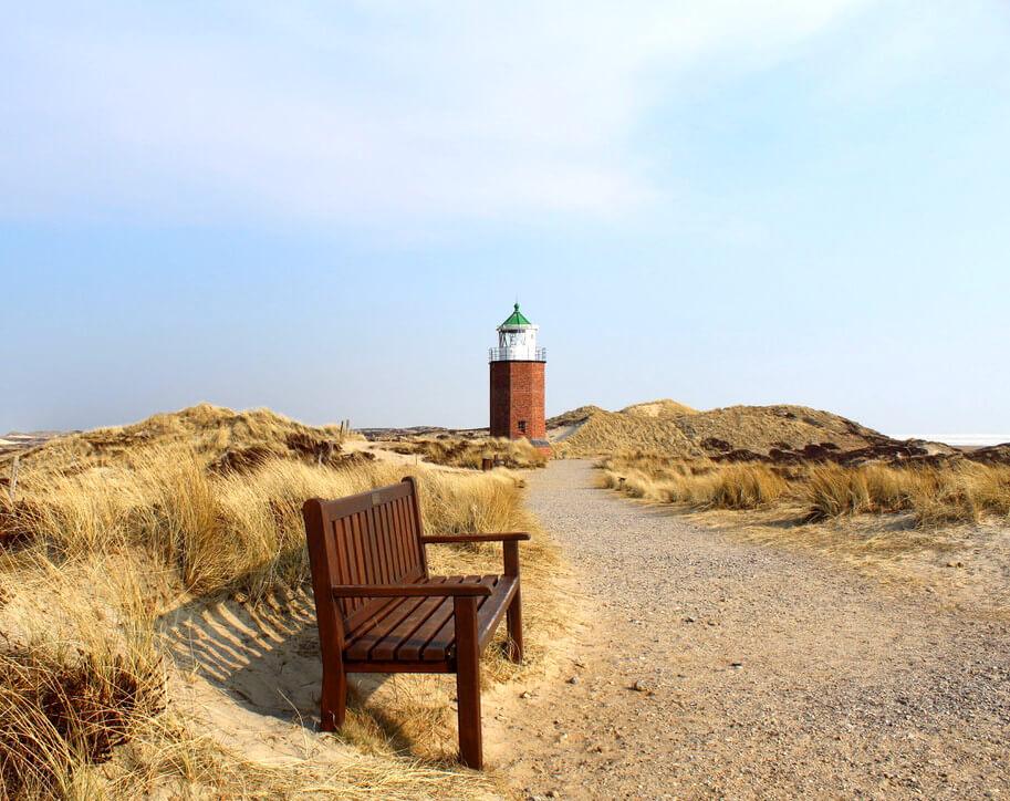 Sitzbank auf Sylt mit Leuchtturm im Hintergrund